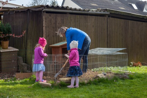 Woman and children cleaning rabbit hutch which is designed to make it easier with plastic slide out trays